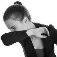 Woman sneezing into her elbow.
