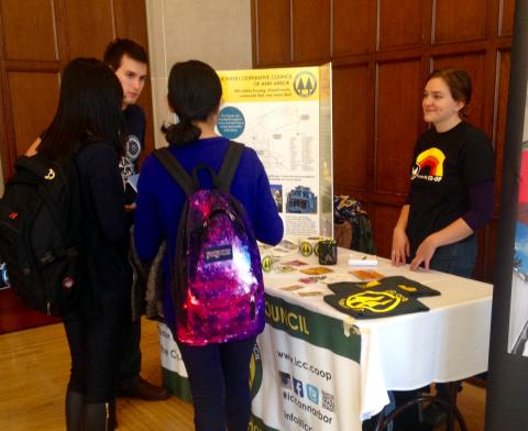 Students talking in front of a table with poster