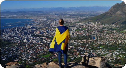 Student covered in a Michigan Flag with a mountainous landscape in the background.