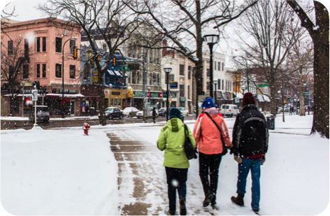 Three people walking from the diag toward State Street shops in the snow.