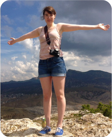 A girl standing on top of a mountain with her arms open.