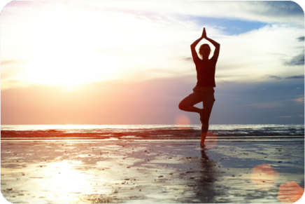 Woman in a yoga pose on the beach with the sunset in the background.