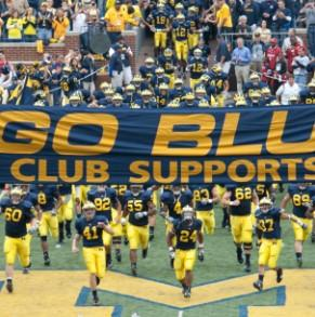 michigan football players running with a banner